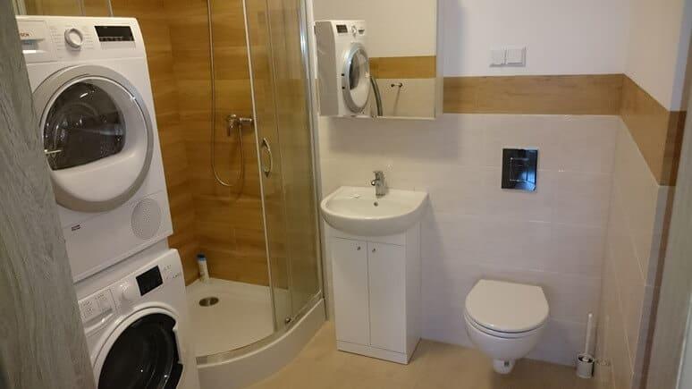 Łazienka z pralką i stojącej na niej suszarką